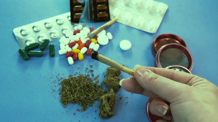 cigarette : Marijuana joint. Pills are on the background Stock Footage