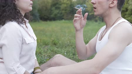 Two young person smoking medical marijuana joint outdoors. The young man and women smoke cannabis blunt, close-up. Cannabis is a concept of herbal medicine. Vídeos
