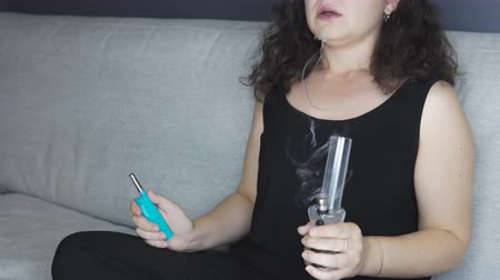 The young person smoking medical marijuana with bong, indoors. The young woman smoke cannabis at home. Cannabis is a concept of herbal medicine.