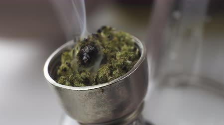 Close-up of smoking medical marijuana with bong, indoors. Macro of smoke cannabis at home. Cannabis is a concept of herbal medicine.