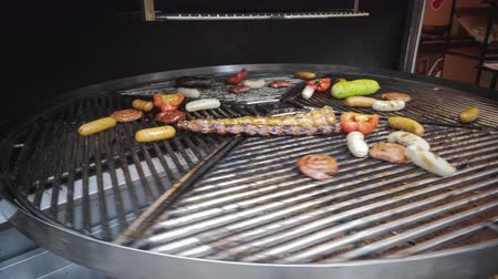 Sliced pepper, zucchini and meat are cooking on grill, outdoors. Picnic with barbecue in the open air. Meat roasted on metal grill.