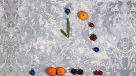 Concept of Christmas and New Year holiday. Flat lay of mandarin, pine cone and Christmas balls in the form of clock. Top view stop motion animation Vídeos