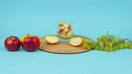 Glass of juice with fresh grape and apples on blue background. Stop motion animation. Concept of diet, healthy eating and using for marketing Vídeos