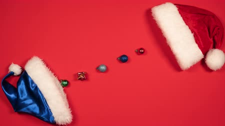 Stop motion animation of New Years balls and Santa Claus hat. Flat lay of Christmas balls and red and blue hat. Top view
