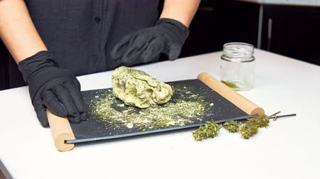 The young female chef preparing to cooking hemp cake or bread. Close-up of fresh dough with cannabis flour. Concept of uses marijuana in a food industry