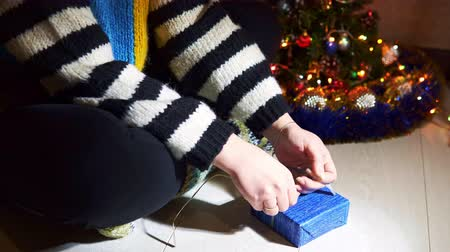 The young woman wrapping Christmas gift with blue paper and ribbon, close-up. Concept of New Years packing presents, art and craft