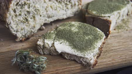 összetevők : Close-up of bread with hemp flour, sandwich with cannabis butter and hashish. Concept of using marijuana in the food industry Stock mozgókép