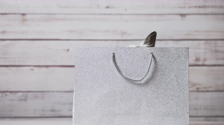 Close-up of cute white bunny is sitting in silver paper bag. Concept of gift and present, Easter and Christmas Holliday