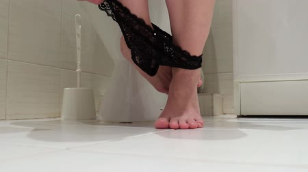 sedes : Cropped legs of a woman, sitting on a toilet with black lowered panties. Concept image of digestive problems and difficulties in the toilet Wideo
