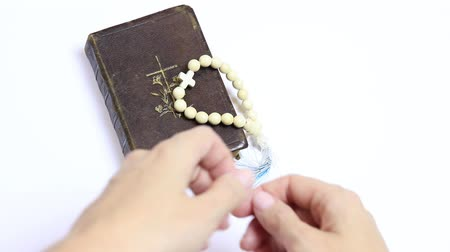 heaven and hell : Hands of a woman putting a Holy Bible and rosary on white table, and folding hands for prayer Stock Footage