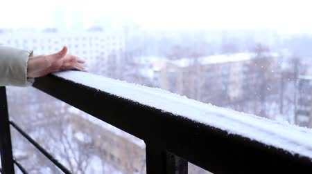 Slowmo video of unrecognisable woman rake, remove snow from the railing, winter city lanscape and snowfall on background