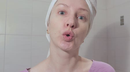 Woman without make up with towel o her head singing a song and shake her head close up