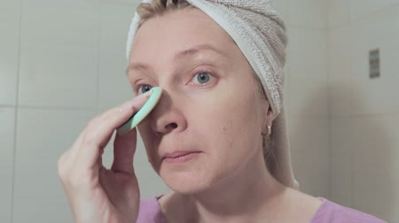 Middle age woman with a towel on her head making up. Shower and make up concept Vídeos