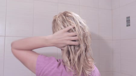 Young woman taking off a towel from her head and shaking her wet hair in bathroom Vídeos