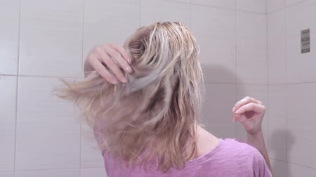 Young woman touching her wet hair in the bathroom