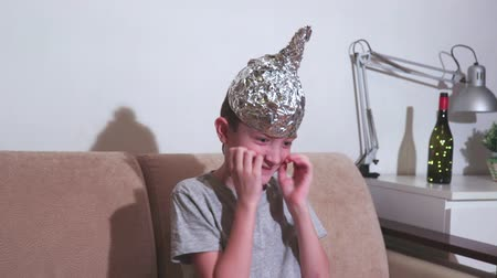 hloupý : Crazy little boy with ugly face expression wearing tin foil cap, hat behaves strangely. He believes that it shields the brain from mind control or reading