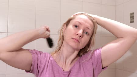 Middle aged blond woman brushing her hair in bathroom Vídeos