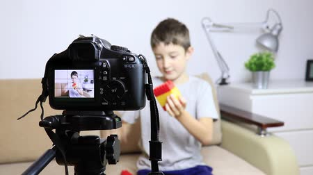 Close up video of camera on tripod with a boy on LCD screen and blurred scene on background. Male child video blogger recording vlog or podcast, streaming online