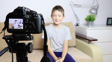 passatempo : Close up video of camera on tripod with a boy on LCD screen and blurred scene on background. Male child video blogger recording vlog or podcast, streaming online