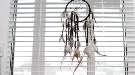 native american culture : Dream protection amulet dreamcatcher of bird feathers hanging on the window with blinds in the morning, serene dreams talisman