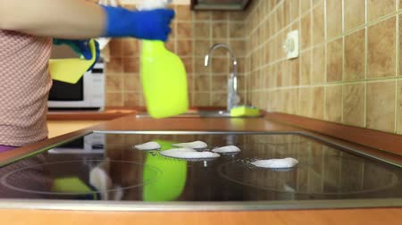 cooktop : Cleaning cooktop cooking panel in kitchen with fat remover spray and a duster by a woman in yellow rubber gloves Stock Footage