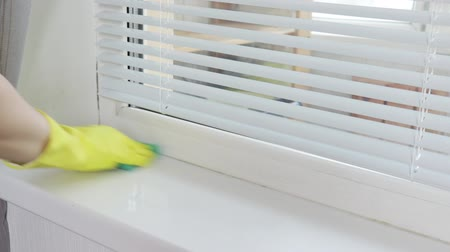 sanitize : Cleaning washing window sill with a sanitary spray and a sponge by a womans hand in yellow rubber glove