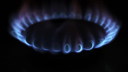 utilidade : Turning on ond off a gas stove in the dark, blue flame burning close up