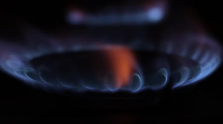 inflamável : Turning on ond off a gas stove, blue flame burning close up