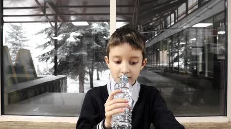 A schoolboy sitting by the table, chewing and drinking water from plastic bottle