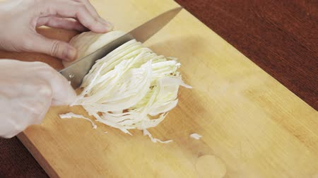 tábua de cortar : A woman cutting a cabbage with a knife on wooden board