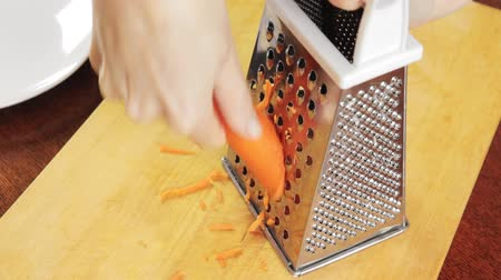 peeler : Woman grates raw carrots on grater on wooden board Stock Footage