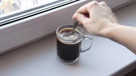 cuisine dark : Woman brews instant coffee in a transparent glass cup on a window sill in the morning and stir it with a spoon Stock Footage