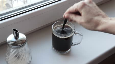 adoçante : Woman adding sugar to a black coffee in transparent clear glass cup in the morning Vídeos