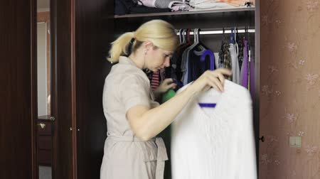 traje de passeio : Young blond woman opening a wardrobe at home and choosing clothes to dress in Stock Footage