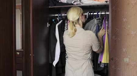 traje de passeio : Young blond woman standing in front of an opened wardrobe at home and choosing clothes to dress in Stock Footage