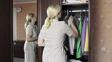 traje de passeio : Young blond woman standing in front of an opened wardrobe at home and unbutton her home dress in order to change clothes