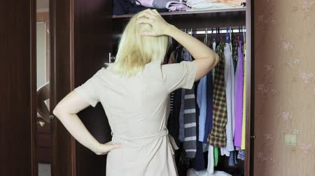 traje de passeio : Undecided young blond woman opening a wardrobe at home and choosing clothes to dress in, she scratching her head and thinking