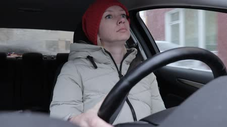 car rental : Woman in winter clothes and orange knitted hat driving a car on winter road