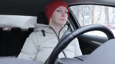 аренда : Woman in winter clothes and orange knitted hat driving a car on winter road