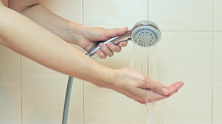 banheira : A womans hand holds a shower head in the bathroom, turns the water on, tries the water temperature and turns it off