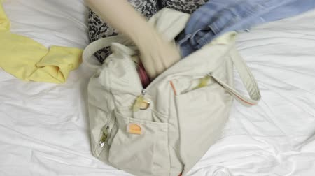 stuff bag : Woman sitting on a bed, opens a bag and taking off clothes in a hurry a laggage bag