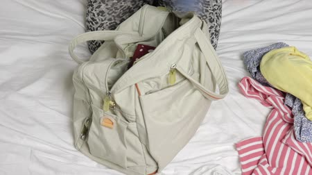 stuff bag : Woman sitting on a bed and putting clothes into a laggage bag, preparing for travelling and journey
