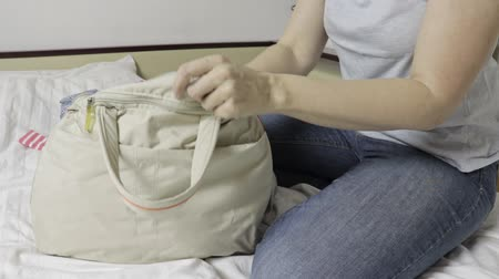 stuff bag : Woman sitting on a bed, opens a bag and taking clothes off a laggage bag