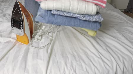 гладильный : Household concept, woman sitting on a bed and putting an iron and a stack of clothes in front of her, close up view Стоковые видеозаписи