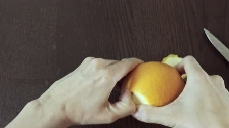 fructose : Womans hand is peelingan orange on a wooden background. easiest and fastest way Stock Footage