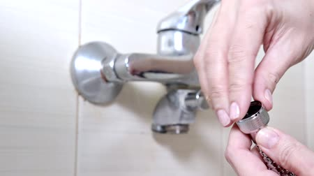 sıkmak : Female hands inserting a rubber gasket into the hose from a bathtub faucet - plumbing repairs and DIY concept