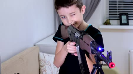 innesco : Portrait preteen boy playing and shooting automatic weapon gun riffle Kalashnikov at home