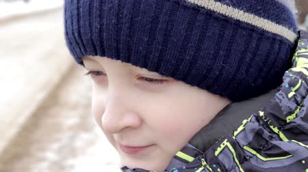 好奇心 : Close up portrait of a beautiful preteen boy with amazing eyes sitting on a bench in park in winter