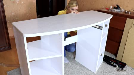 арматура : Woman mounting new white furniture, she putting a tabletop on a new half assembled dressing table