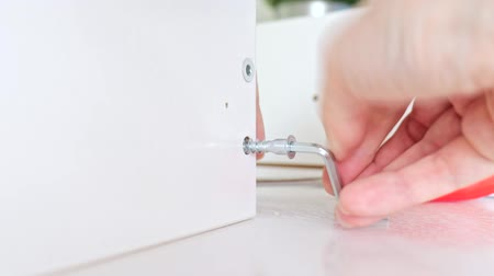 do it yourself : Close up view of a person assembling new white drawer using a screwdriver, tighten a screw with a hex allen key